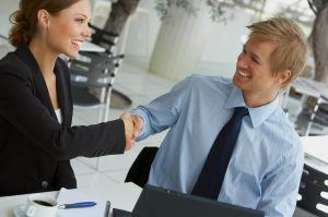A businesswoman and businessman shaking hands.