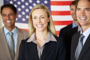 Portrait of confident business associates smiling with flag in background